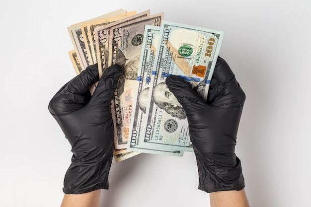 Hands in medical gloves holding a pack of dollars. the concept of infection for money, dirty money