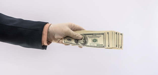 Hands in medical gloves holding stack dollars for safety, dirty money epidemic. all for health