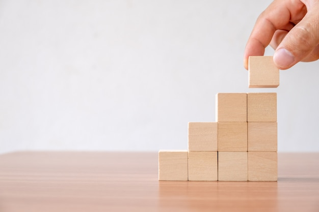 Hands of men arranging wood cube block stacking for top staircase shape on wooden table.