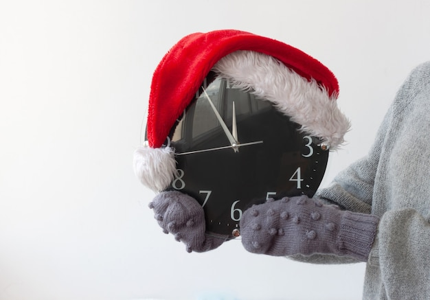 Hands in mittens are holding the clock on which the santa claus hat is worn