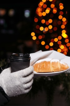 Hands in mittens hold a hot cup of coffee and a croissant. coffee to go in winter.