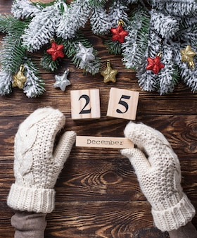 Hands in mittens holding wooden calendar