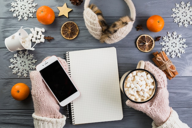 Hands in mittens with smartphone and cup with marshmallow near notebook and paper snowflakes