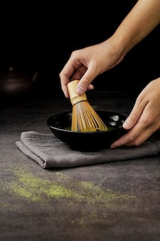 Hands mixing matcha tea in bowl with bamboo whisk