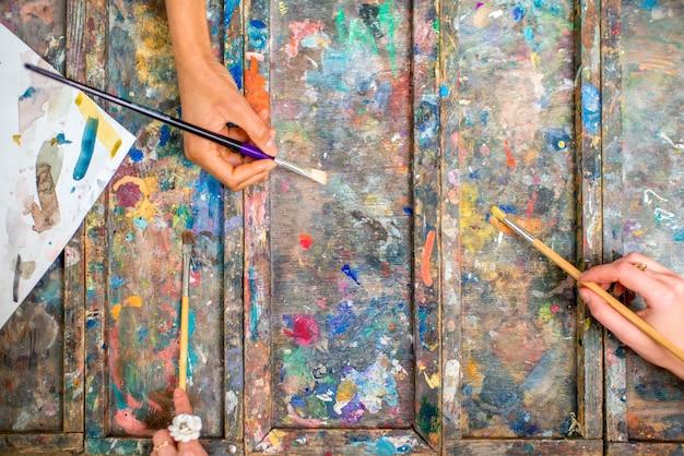 パレット上のブラシで絵の具を混ぜる手