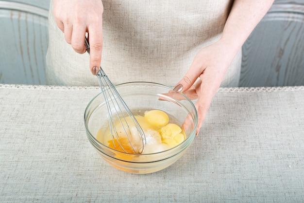 Руки смешивают сырые яйца и сахар в стеклянной миске металлическим венчиком