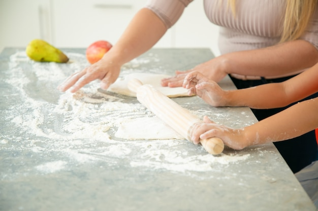 Mani di mamma e figlia che rotolano la pasta sul tavolo della cucina. ragazza e sua madre che cuociono insieme il pane o la torta. primo piano, colpo ritagliato. concetto di cucina familiare