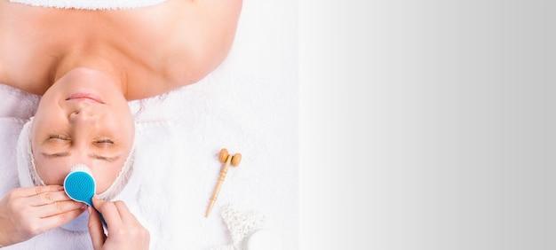 얼굴 마사지를 사용하는 노인 여성의 얼굴을 mossing 손. 흰색 배경 및 빈