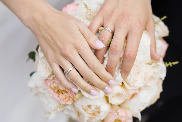 Hands of the newlyweds, the bride and groom, with wedding rings on a wedding bouquet of white and milk roses and peonies close-up. wedding couple