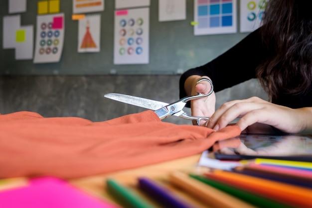 Рука вырезать портной портной ножницы ткани резки кусок ткани (концепция модельера).