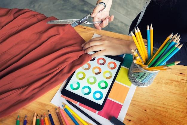 ファッションデザイナーコンセプトのファブリックをカットするハンドノッチテーラーのはさみ布。