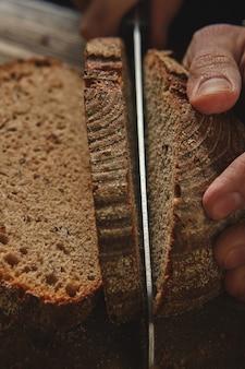 パン屋の男の手が木の板に田舎の暗いパンを切りました