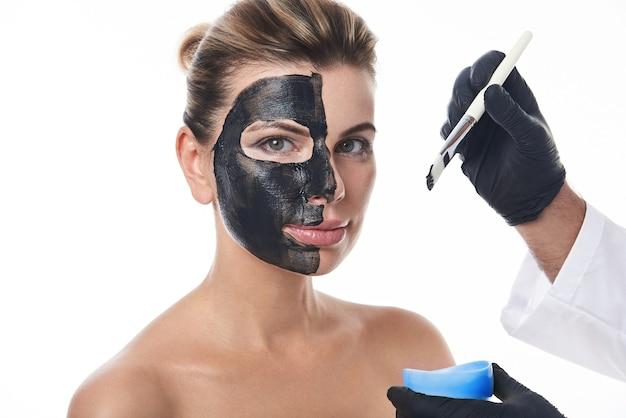 Руки косметолога в черных медицинских перчатках держат косметическую кисть и наносят очищающую маску с черным углем.