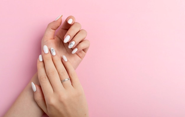 Руки красивой ухоженной женщины с женственными ногтями на розовом фоне. маникюр, концепция салона красоты педикюра. пустое пространство для текста или логотипа. на ногтях белый гель лак с абстрактным
