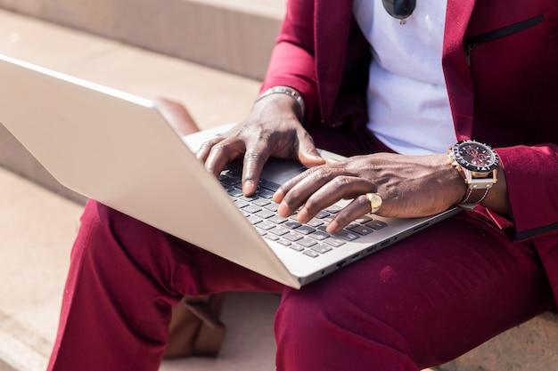 彼のラップトップで作業している黒人男性の手