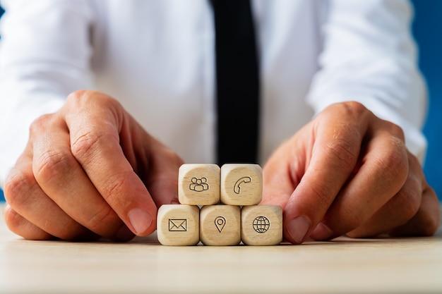 顧客サービスの連絡先とコミュニケーションのアイコンが付いた木製のサイコロを持っているビジネスマンの手。