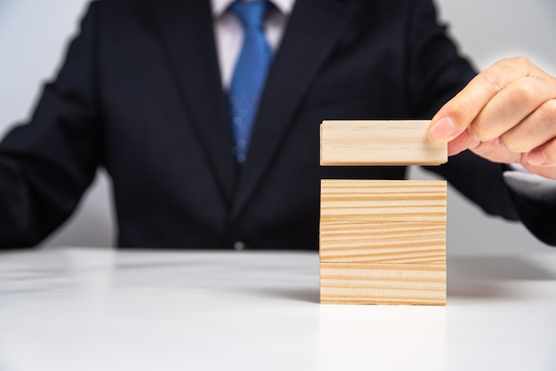 Руки бизнесмена штабелируя деревянные блоки на таблице. бизнес-концепция