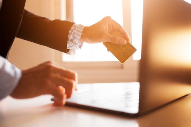 インターネット上でラップトップとカードを使用してビジネスマンの手