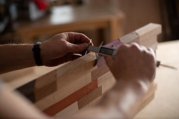 大工の手は、ノギスの助けを借りて木の丸太を測定します。