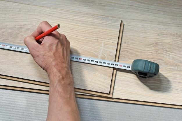 ウッドラミネートフローリングを測定する大工の手