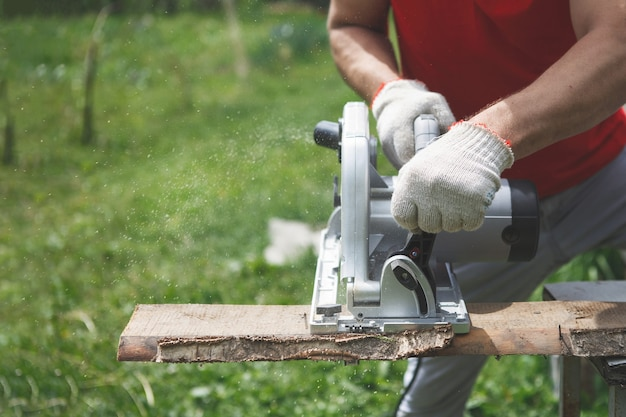 Руки плотника в перчатках распиливают электрической дисковой пилой. красная футболка, серые брюки, на фоне зеленой травы и деревьев. ручная работа, строительство домов, инструменты.