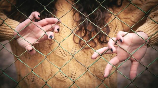 金網上の白人の女の子の手。