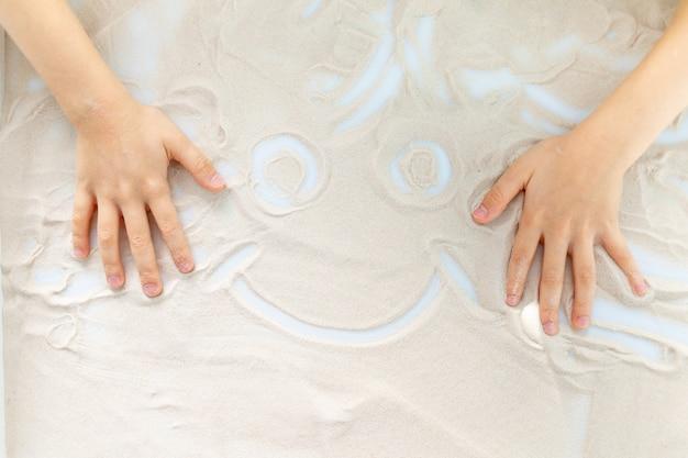 모래에 미소를 그리는 아이의 손