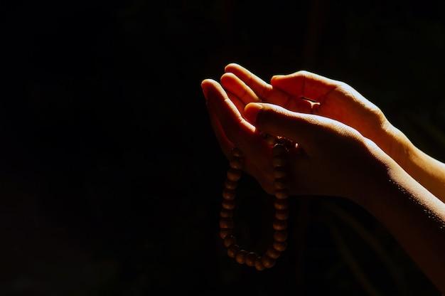 어두운 배경과 역광에 염주로 기도하는 아이의 손