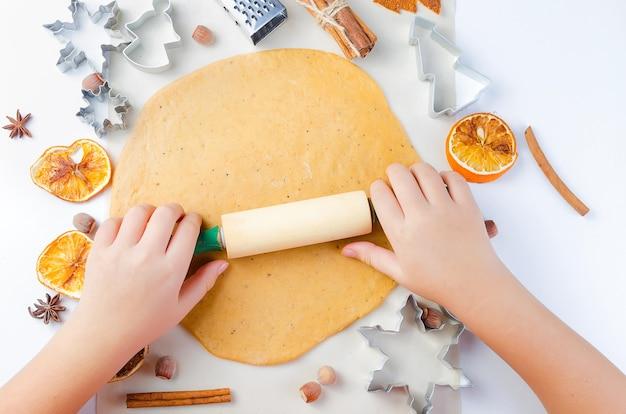 크리스마스 진저 쿠키 반죽에 롤링 핀을 가진 아이의 손