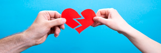 青い背景に傷ついた心を持つカップル、男性と女性の手。離婚の概念。