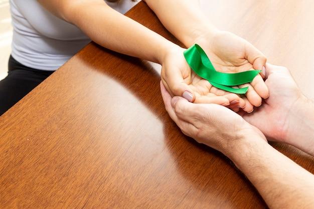 緑のリボンを保持しているテーブルの上のカップルの手。