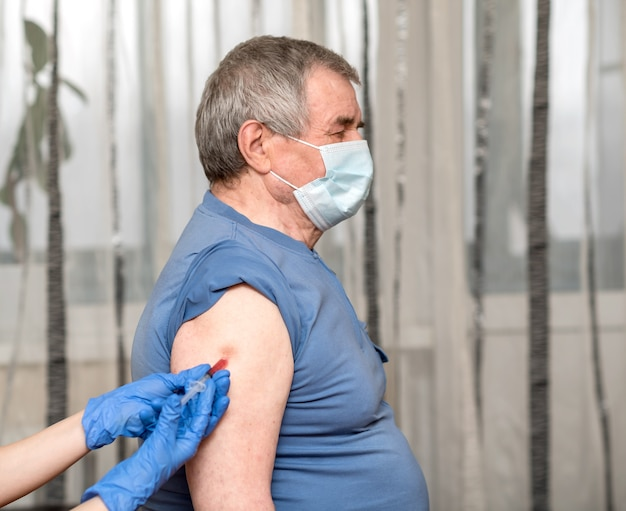青い手袋をはめた医者の手が老人にワクチンを与えます。クリニックでは、クローズアップ
