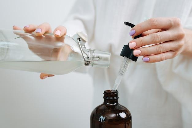 Руки женщины-химика готовят смесь для экологически чистой косметики на столе. одновременно добавляем жидкости из пипетки и стеклянной бутылки.