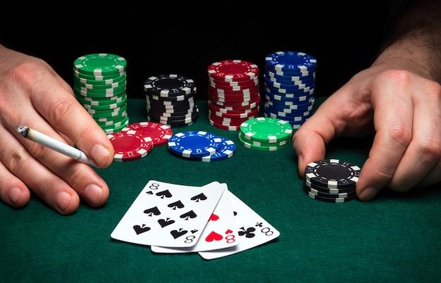 ポーカークラブの緑のテーブルにギャンブラーのクローズアップとチップの手