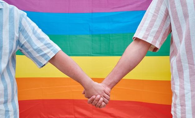 レインボープライドフラグを持つ同性愛者のカップルの手
