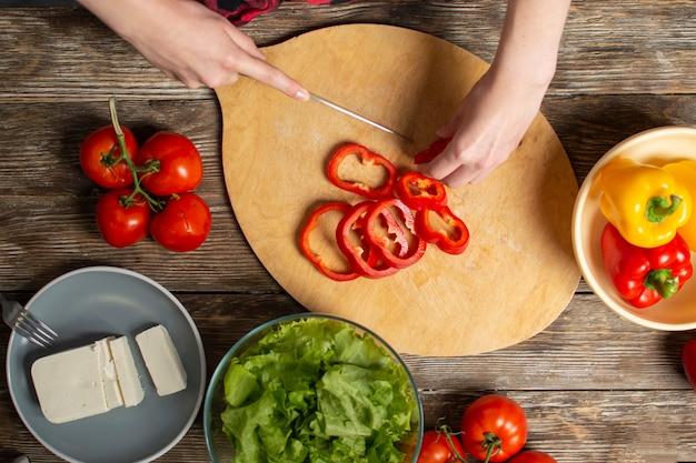 女の子の手は、木製のテーブル、ベジタリアンサラダ、野菜のクローズアップカットを作るプロセスでピーマンをカット