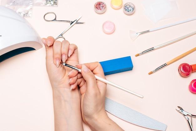 Руки девушки делают маникюр, наносят гель с помощью кисти. вид сверху