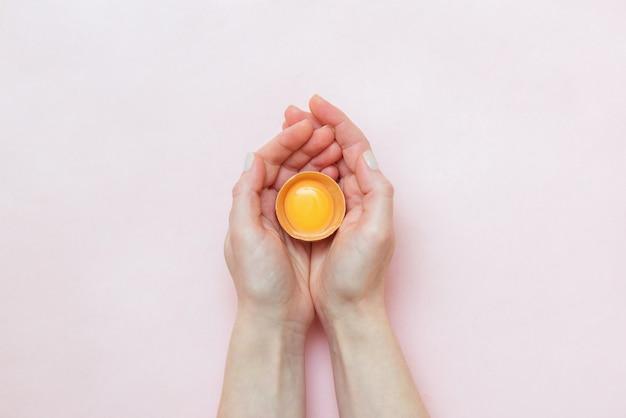 Руки девушки, держащей натуральное сырое сломанное яйцо на розовом фоне. абстрактный образ семьи, рождения детей. концепция экстракорпорального оплодотворения. концепция эко. проблема бесплодия