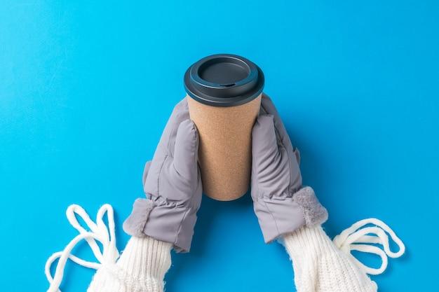 Руки девушки в белом свитере и рукавицах с бумажным стаканчиком кофе на синей поверхности. горячий напиток и варежки.