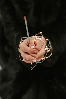 線香花火のクローズアップを持つ少女の手