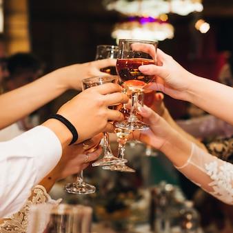 レストランでお祝いパーティーで赤ワインのグラスをチリンと乾杯の人々のグループの手