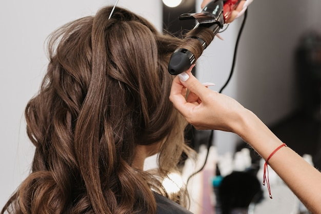 Руки парикмахера с щипцами для завивки делают прическу для кудрявой девушки в профессиональном салоне красоты