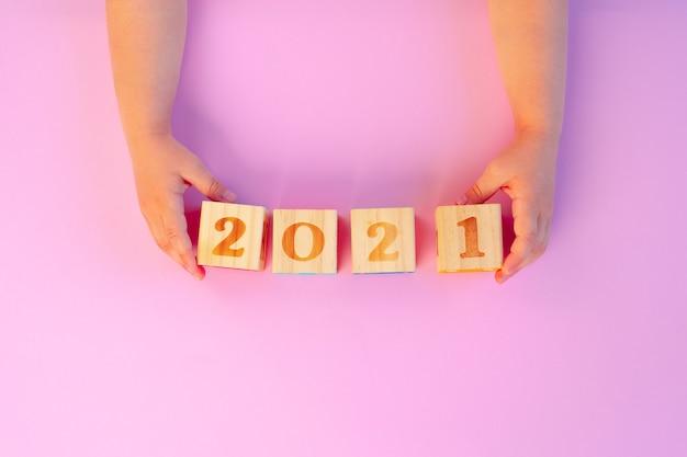 ピンクの年の木製の立方体を保持している子供の手