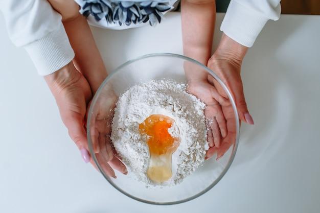 ケーキを作るために小麦粉と壊れた卵でガラス容器を握りしめる少女と母親の手