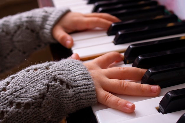 ピアノ音楽を演奏しようとしている少女の手