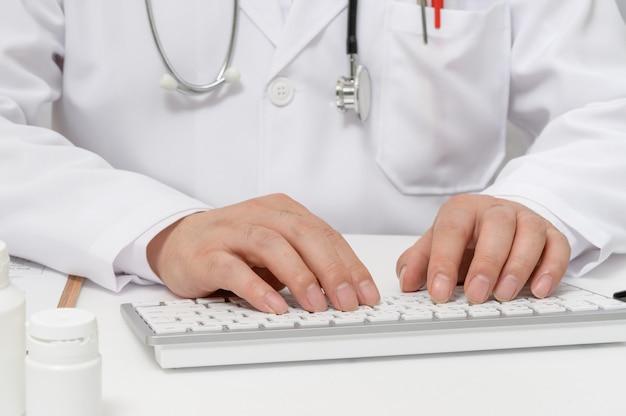 Руки мужского доктора, который использует клавиатуру компьютера.
