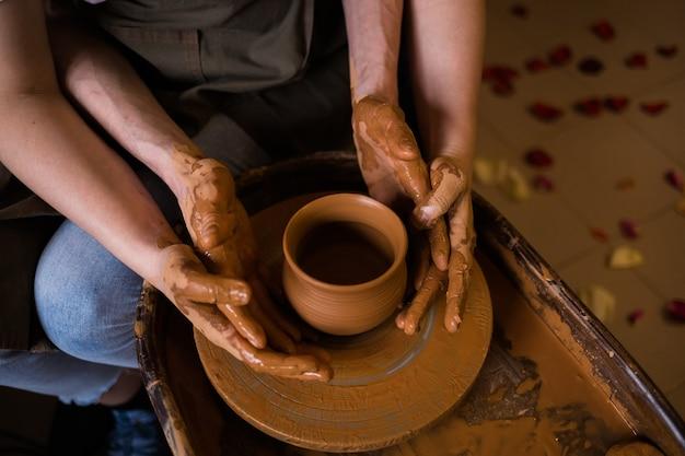한 남자와 한 여자의 손이 방의 베틀에 점토로 그릇을 만든다.