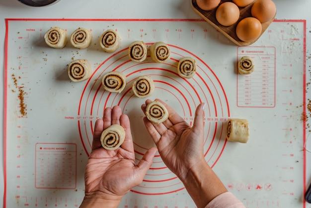 Руки мужчины и женщины готовят булочки с корицей.