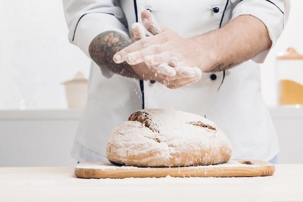남자의 손과 나무 테이블에 갓 구운 빵. 부드러운 빛