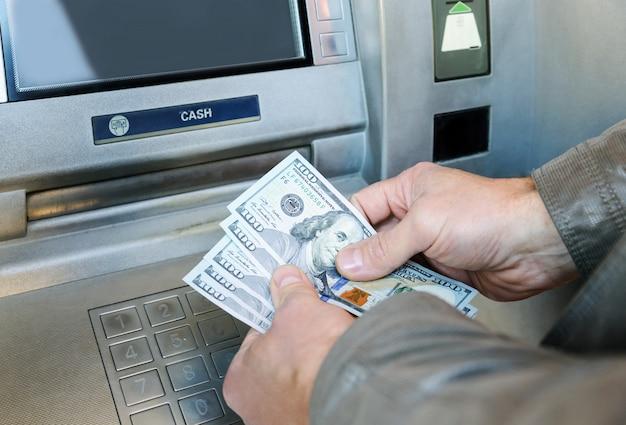 男の手が紙幣を持っています。